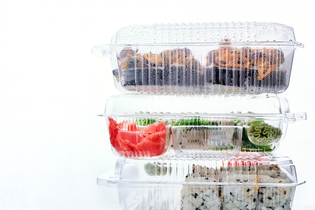 Stack of plastic boxes with sushi roll sets. food delivery