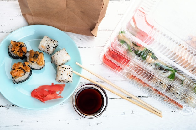 Stack of plastic boxes with sushi roll sets, plate with rolls and paper bag. food delivery