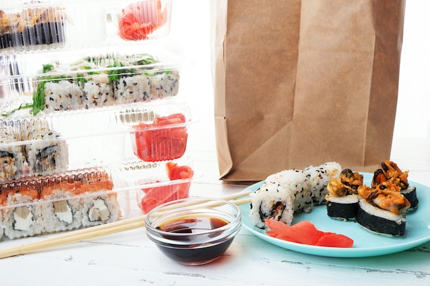 Stack of plastic boxes with sushi roll sets, plate with rolls and paper bag