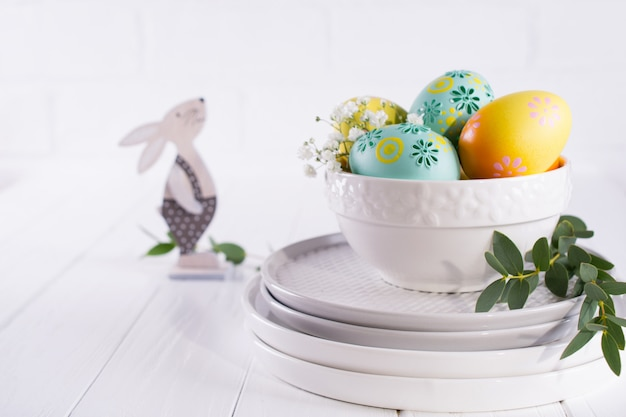 Stack of plates and bowl with colorful easter eggs, spring  easter decoration on white wooden table