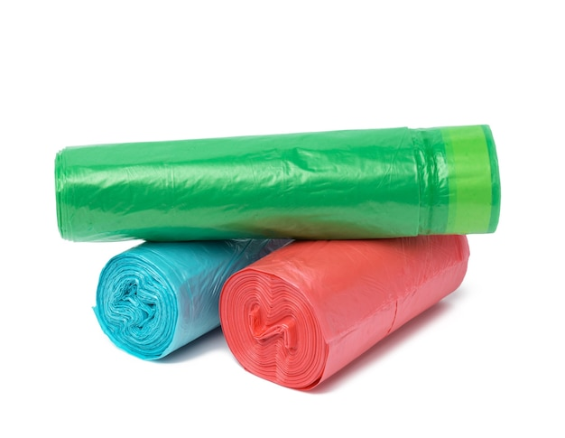 Stack of polyethylene multicolored disposable trash bags on white surface, close up