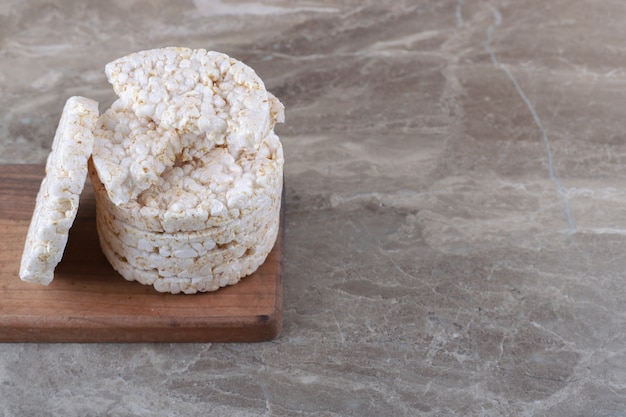 A stack of puffed rice cakes on the wooden tray, on the marble background.
