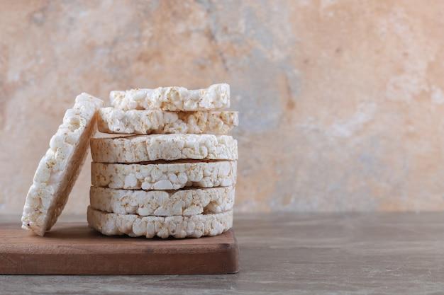 Una pila di torte di riso soffiato sul vassoio di legno, sulla superficie di marmo