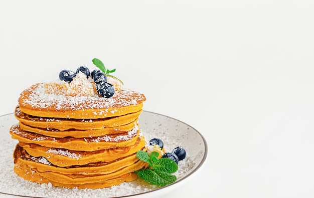 Stack of pumpkin pancakes with blueberries and mint. copy space