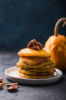 Stack of pumpkin pancakes with caramel sauce and pecan nuts