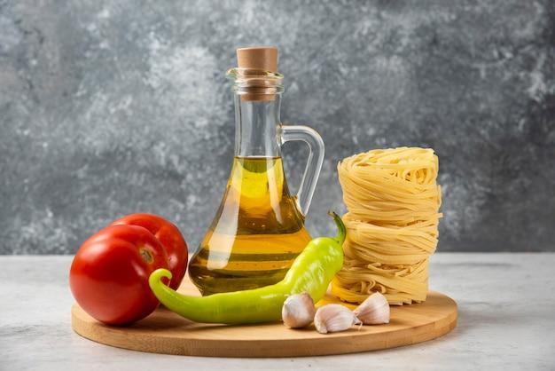 Pila di nidi di pasta cruda, bottiglia di olio d'oliva e verdure sul piatto di legno.