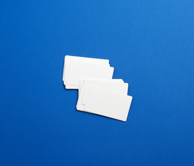 Stack of rectangular white blank business cards on a blue