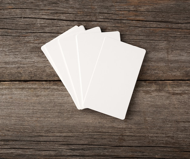 Stack of rectangular white blank business cards on a gray wooden background