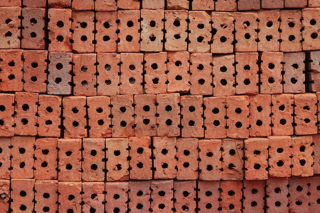 Stack the red bricks that are arranged in the background for construction