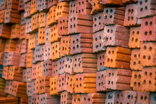 Stack the red bricks that are arranged for construction
