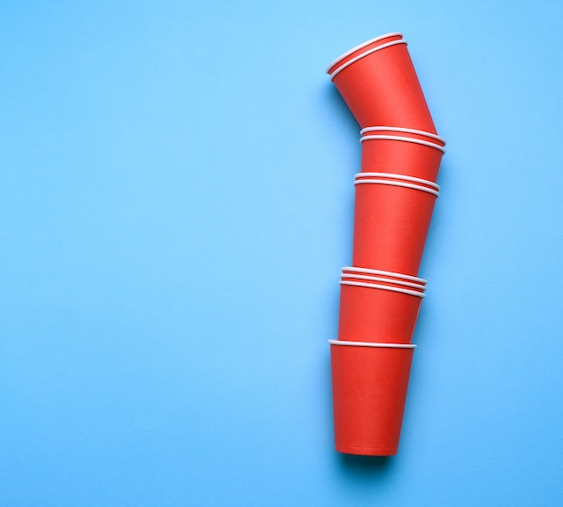 Stack of red paper disposable cups on a blue background