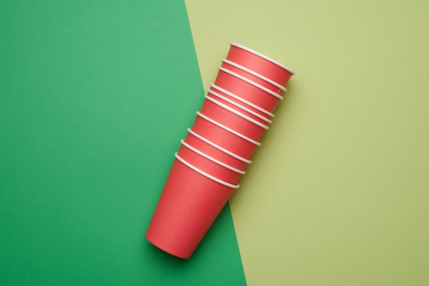Stack of red paper disposable cups on a green background, flat lay