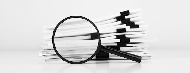 Stack of report paper documents with magnifying glass. concept of business and search.