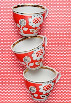 Stack of retro cups with red patterns on tablecloth whith polka dots