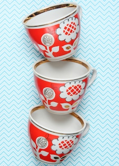 Stack of retro cups with red patterns on tablecloth