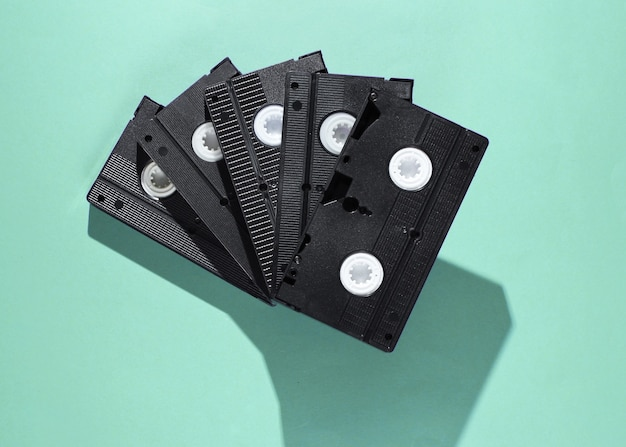 Stack of retro video cassettes on blue