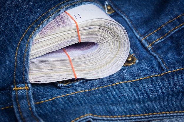 Stack of ringgit banknotes money inside blue jeans pocket