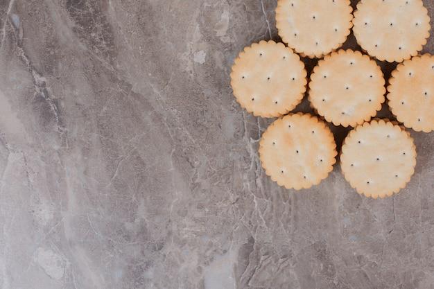 Pila di cracker rotondi sulla superficie di marmo.