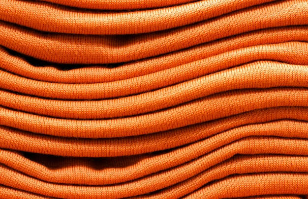 Stack of russet orange woolen knitted sweaters close-up