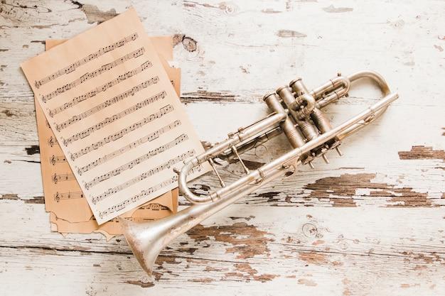 Stack of sheet music near trumpet