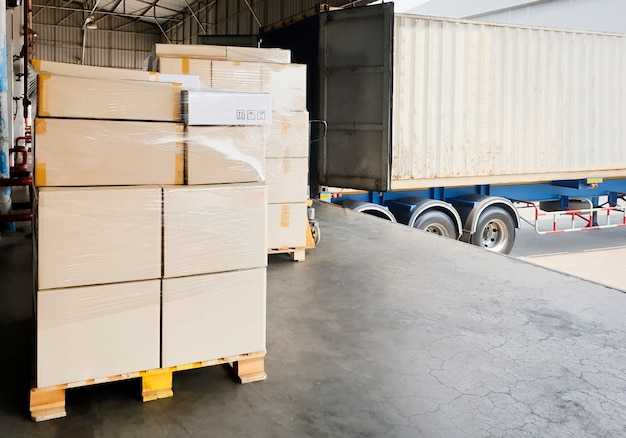 Stack of shipment boxes pallet waiting for load into container truck. road freight shipment transport by truck.