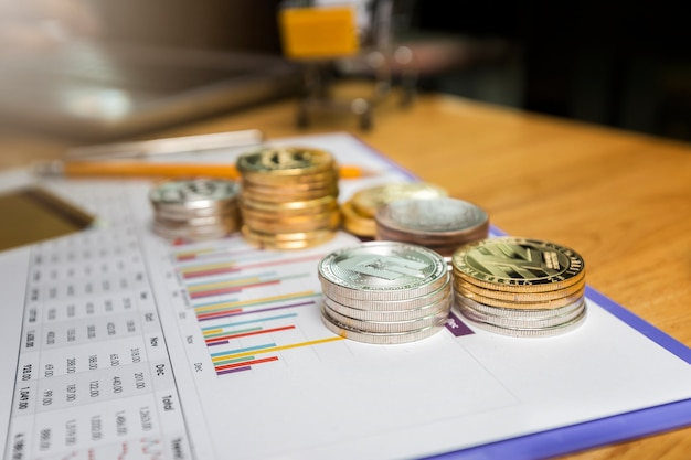 Stack of silver dashcoins and golden litecoins (cryptocurrency) on paper graph.