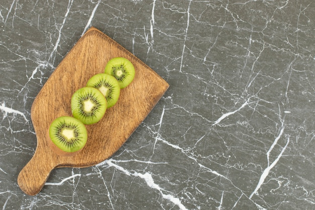 Stack of sliced kiwi on wooden cutting board.