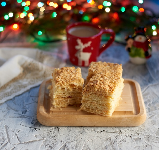 Stack of slices of napoleon cake made of puff pastry and butter cream near of christmas decoration
