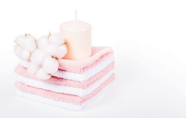 Stack of soft towels, candle and cotton flowers