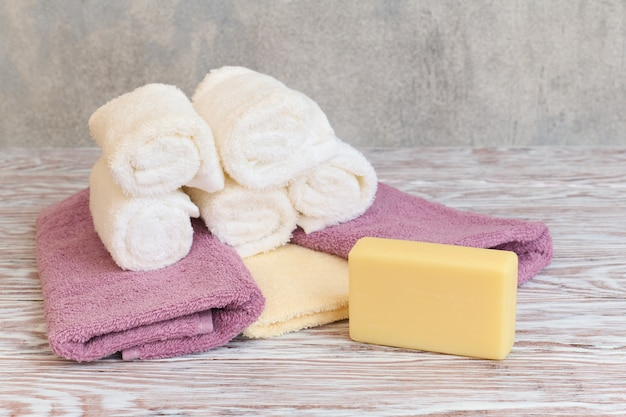 Stack of spa terry towel and soap bar on wooden table