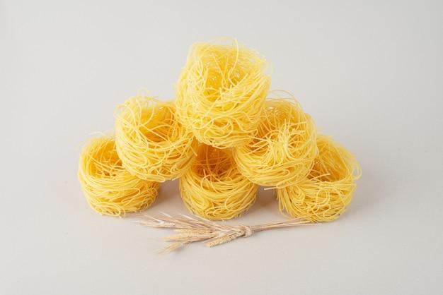 Pila di nidi di spaghetti sulla superficie bianca con grano