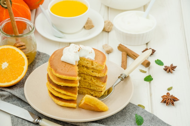 Stack of spicy pumpkin pancakes on a plate with honey and whipped cream on a white wooden surface