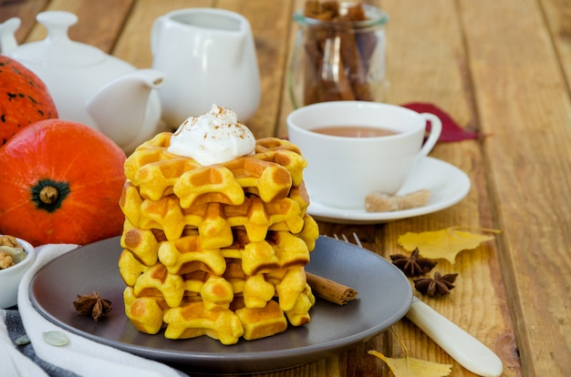 Stack of spicy pumpkin waffles on a dark plate with caramel sauce and whipped cream