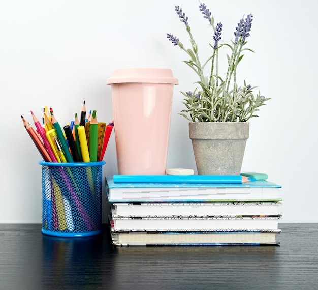 Stack of spiral notebooks with white pages and ceramic pots with plants