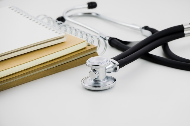 Stack of spiral notepad and stethoscope on white backdrop