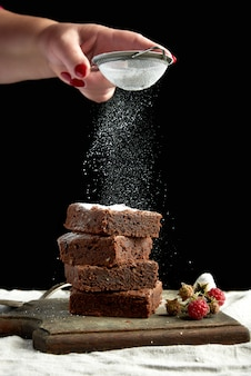 Stack of square baked brownie chocolate cake slices sprinkled with white sugar