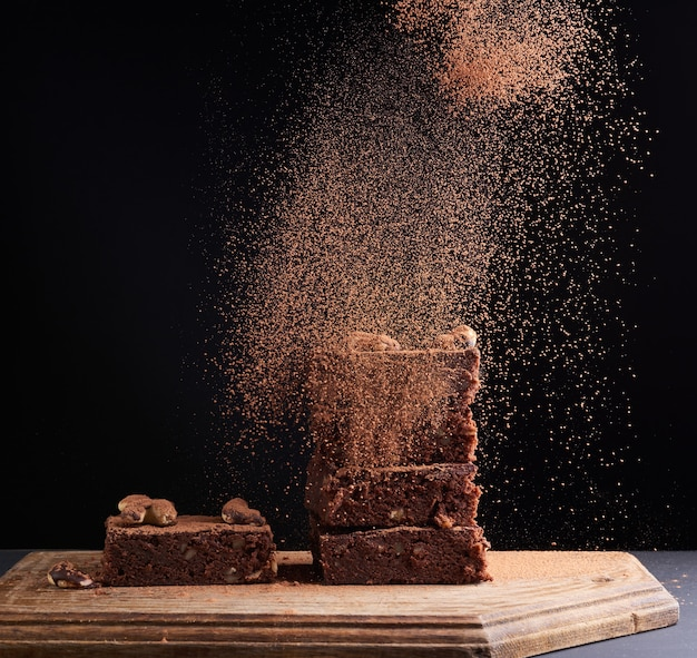 Stack of square baked brownie pieces sprinkled with cocoa powder