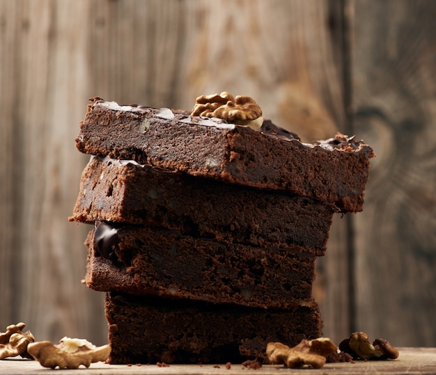 Stack of square baked slices of brownie chocolate cake with walnuts on a wooden surface