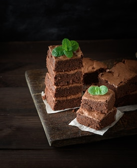 Stack of square pieces of baked brown brownie pie on a wooden  board, on the top is a green mint leaf