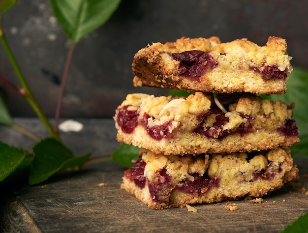 Stack of square pieces of crumble pie with cherry on a wooden board