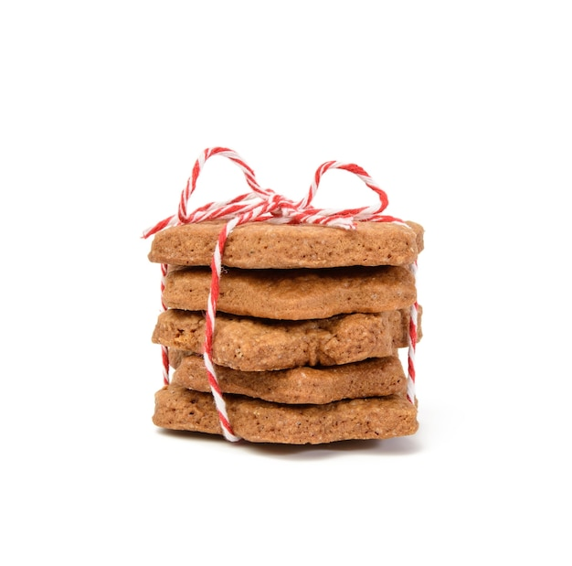 Stack of star shaped baked chocolate gingerbread cookies tied with red rope and isolated on white background