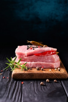 Stack of steaks of fresh raw pork meat decorated with chili peppers and rosemary on a dark.