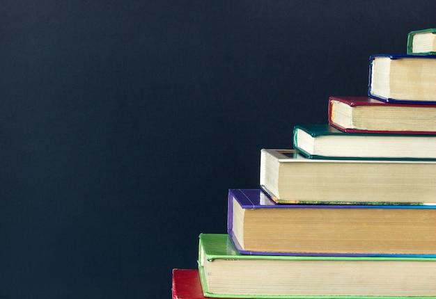 배경 검은 칠판에 오래 된 책의 스택 단계 계단