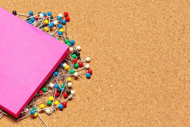 Stack of sticky notes surrounded with a bunch of colorful push pins