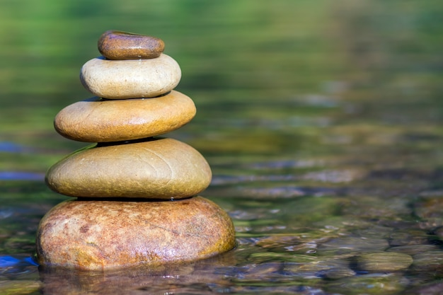Stack of stones balancing on top in green water of the river