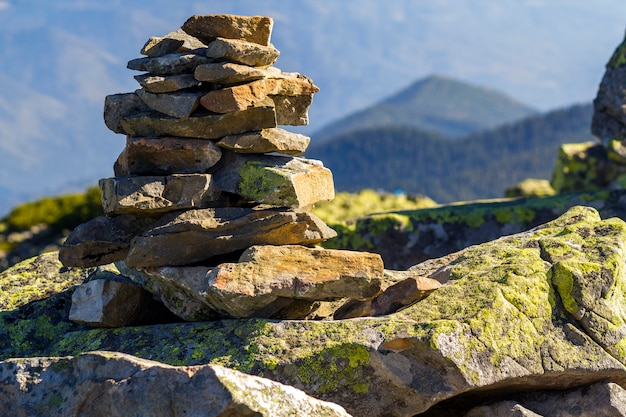 Stack of stones covered with moss on top of a mountain on mountains. concept of balance and harmony. stack of zen rocks. wild nature and geology detail.