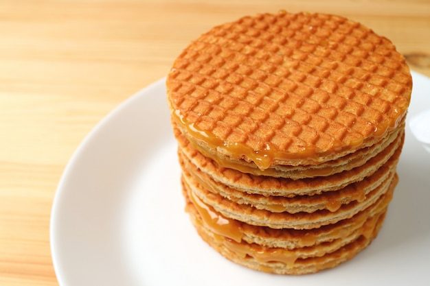 Stack of stroopwafel on the white plate served on wooden table