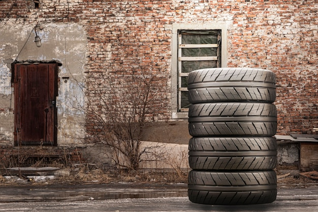 Stack of summer tires against a brick wall