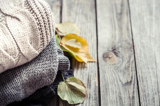 Una pila di maglioni e foglie d'autunno