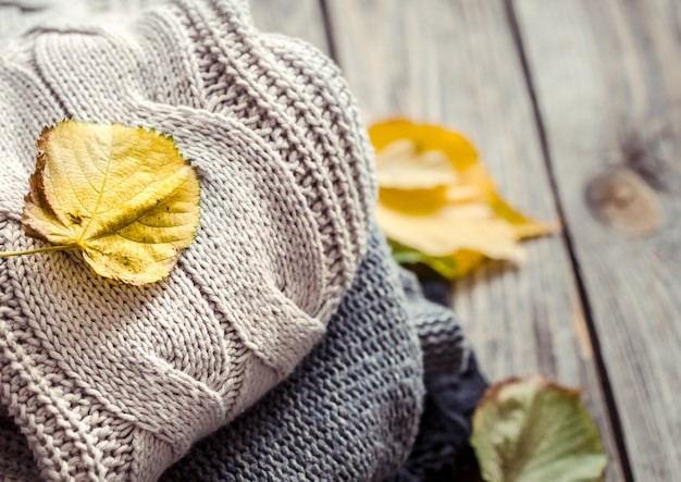 A stack of sweaters and autumn leaves